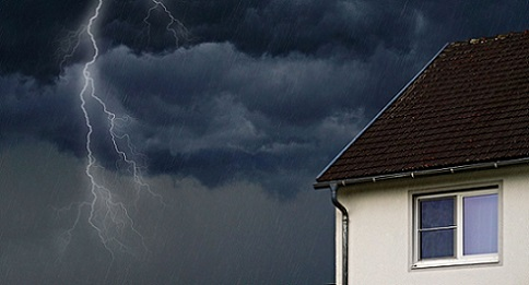 Ein Blitz neben einem weißen Haus mit braunen Dachziegeln.