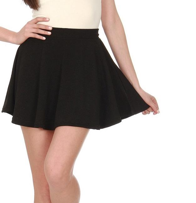 Unterkörper einer jungen Frau in einem schwarzen Rock.