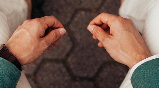 Zwei Arbeiterhände eines älteren Mannes aus der Vogelperspektive.