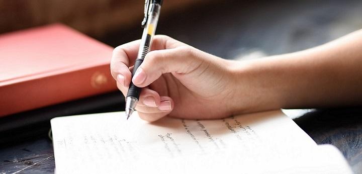 Liebes Tagebuch. Frau hält einen Stift in der Hand und schreibt etwas in ihr Tagebuch.