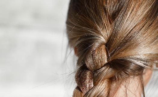 Frau mit dunkelblondem Haar und einem Zopf.