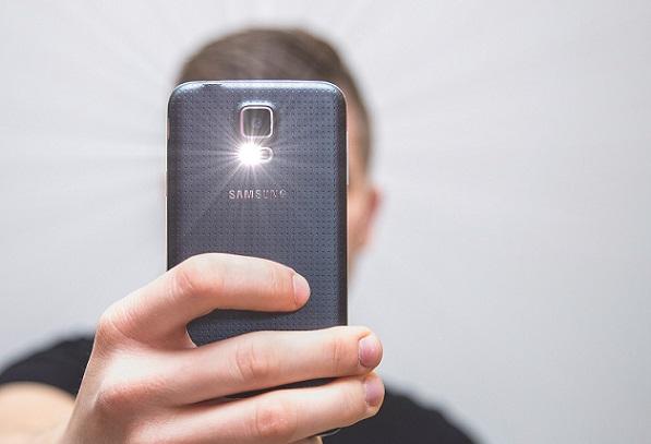 Foto von einem jungen Mann, der mit seinem Smartphone ein Bild macht.