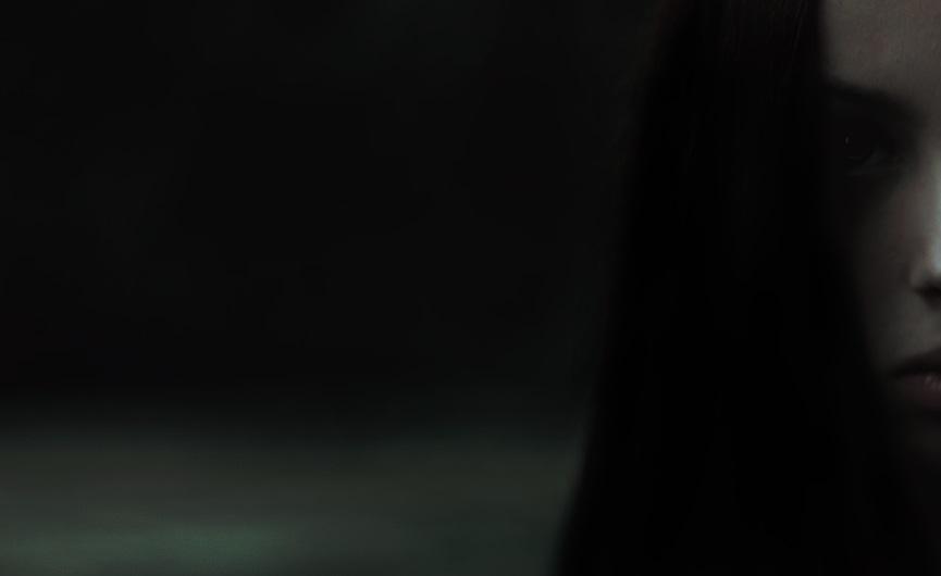 Gesicht eines Mädchen mit schwarzen Haaren in der Dunkelheit.