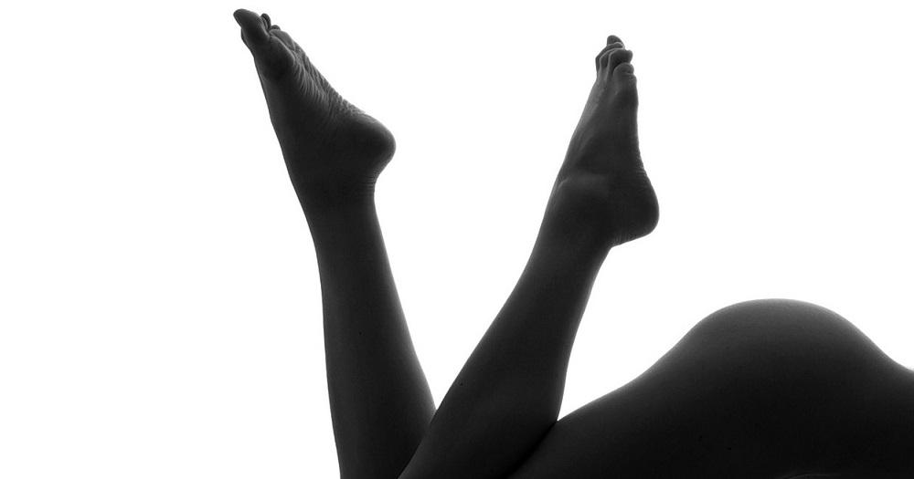 Schwarz-weiß Bild von den nackten Füßen, Beinen und dem blanken Hintern einer jungen Frau.