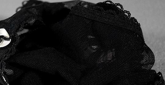 Ein schwarzer Slip auf einem weißen Teppich.