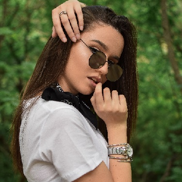 Foto einer hübschen, jungen Frau in einem weißen T-Shirt, mit dunkelbraunen Haaren, einer Sonnenbrille, einem Ring am linken Mittelfinger und einer silbernen Uhr am rechten Handgelenk, die in die Kamera schaut.