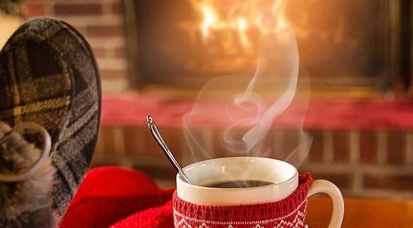 Bildausschnitt mit einem Pantoffel, einer dampfenden Tasse Glühwein und einem brennenden Kamin in Weihnachtsstimmung.