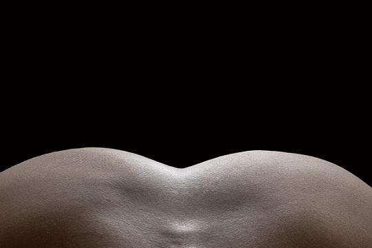 Rundungen eines weiblichen Hintern vor einem schwarzen Hintergrund.