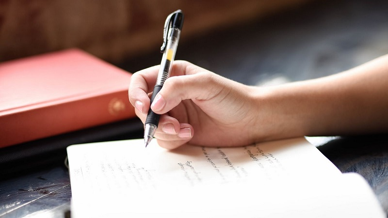 Liebes Tagebuch. Frau hält einen Stift in der rechten Hand und schreibt etwas in ihr Tagebuch.
