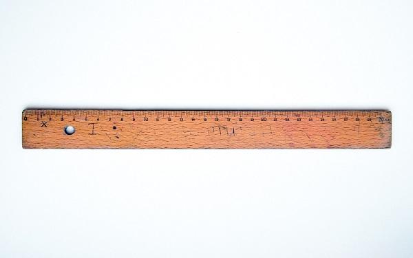 Ein abgenutztes Holzlineal auf einem weißen Untergrund.