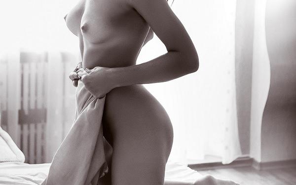 Bild einer nackten Frau, die auf dem Bett kniet und sich eine Decke vor den entblößten Körper hält.