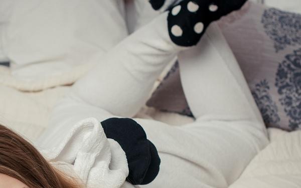 Junge Frau liegt in einem weißen Schlafanzug und mit schwarzen Socken mit weißen Punkten auf dem Bett.