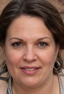 Porträt von Silke Lottner. Etwas dicke Frau im mittleren Alter mit braunen Augen, zwei Ohrringen, dunkelbraunen Haaren und einem verhaltenen Lächeln auf den Lippen.