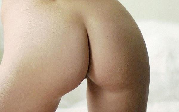 Nackter Hintern einer jungen Frau vor einem weißen Hintergrund.