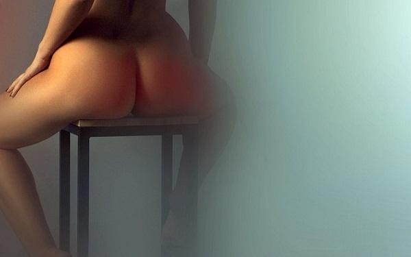 Nackte Frau sitzt auf einem Hocker und präsentiert ihren versohlten Hintern.